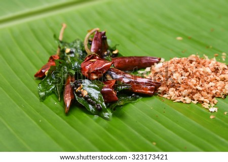 vattal mulaku, Kashmiri/Kashmiry, chili pepper/chile/chilli pepper on a banana leaf, genus Capsicum. Dry red chilly pepper, curry leaves for seasoning  sambar, chutney, curry. Kerala,Tamil Cusines  - stock photo