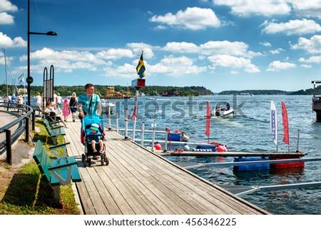 VAXHOLM, SWEDEN - JUNE 25, 2016: People walking at seaside at little cosy island Vaxholm near Stockholm - stock photo