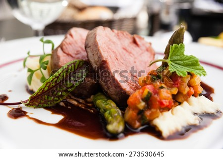Veal fillet with vegetable ratatouille, parsnip puree, asparagus and bone marrow sauce - stock photo