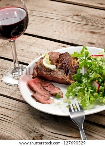 Veal meat with green salad with a red wine glass - stock photo