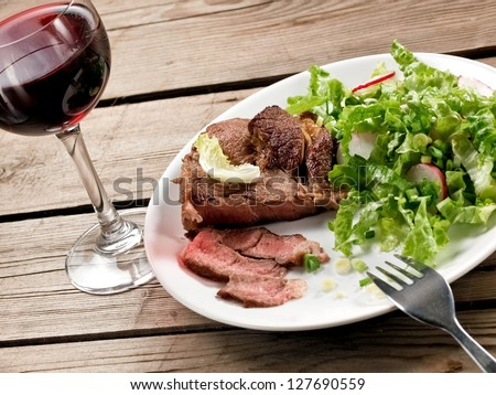 Veal meat with green salad with a red wine glass, horizontal view - stock photo