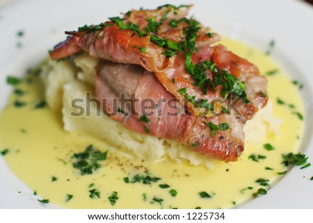 Veal Scallopine wrapped in prosciutto on creamy mash with Beure blanc. Close crop landscape from above. - stock photo
