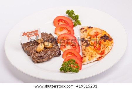 veal steak with tomatoes and Calzone - stock photo