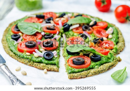 vegan broccoli zucchini pizza crust with spinach pesto, tomatoes, onion and olives. toning. selective focus - stock photo