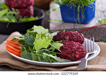 Vegan burgers with beetroot and red beans served with salad - stock photo
