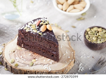 Vegan chocolate beet cake with avocado frosting, decorated with nuts and seeds - stock photo