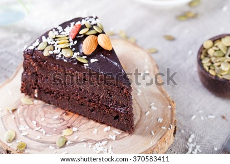Vegan chocolate beet cake with avocado frosting, decorated with nuts and seeds