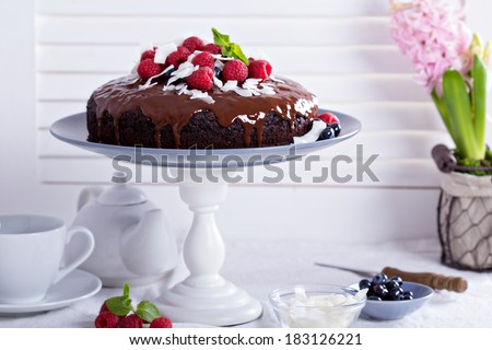Vegan chocolate cake with berries and coconut on top - stock photo