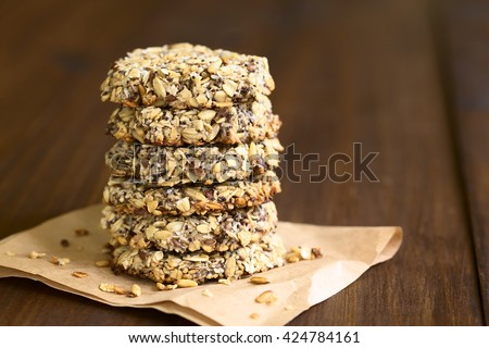 Vegan cookies made of banana, oatmeal, roasted oat grains, linseed, poppy seeds, grated coconut, chia seeds, photographed with natural light (Selective Focus, Focus on the front of the cookies)