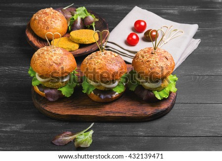 Vegan double burgers with vegetables, onion, vegetable cutlets, lettuce, sauce, ingredients for cooking vegan burgers cherry tomatoes, lettuce, rolls, skewers, wooden surface of dark black background - stock photo
