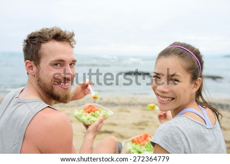 Vegan friends eating vegetarian salad meal during lunch break on beach happy looking at camera. Multiethnic group of young people, Caucasian man, Asian chinese mixed race woman in their 20s. - stock photo