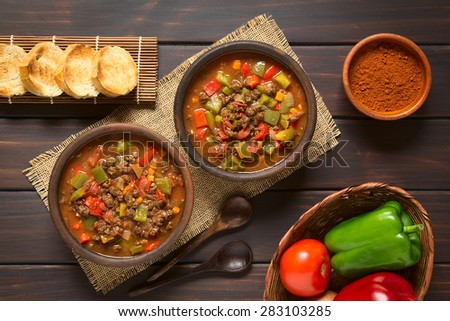 Vegan goulash made of soy meat (textured vegetable protein), capsicum, tomato, onion in rustic bowls, toasted bread, ingredients on the side, photographed overhead on dark wood with natural light - stock photo