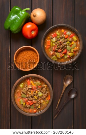 Vegan goulash made of soy meat (textured vegetable protein), capsicum, tomato, onion in rustic bowls, paprika powder, vegetable, spoon on side, photographed overhead on dark wood with natural light - stock photo