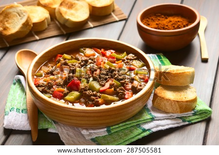 Vegan goulash made of soy meat (textured vegetable protein), capsicum, tomato, onion in wooden bowl with toasted bread, photographed with natural light (Selective Focus, Focus one third into the dish) - stock photo
