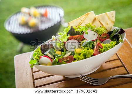Vegan Healthy fresh leafy green salad in a white ceramic bowl on a wooden picnic table in the sunshine at a summer garden barbecue - stock photo