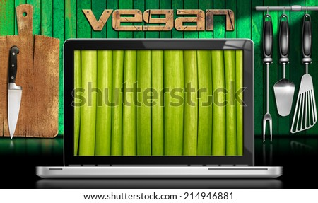 Vegan Kitchen - Laptop Computer / Laptop computer with green vegetables in the screen in a kitchen with cutting board and utensils on wooden green wall. Concept of vegan cuisine - stock photo