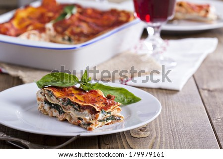 Vegan lasagna with tofu, tomato sauce and spinach - stock photo