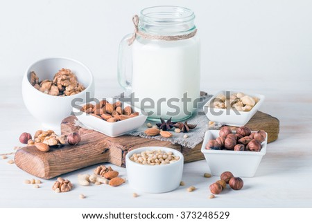 Vegan milk from nuts in glass jar with various nuts on white wooden background - stock photo