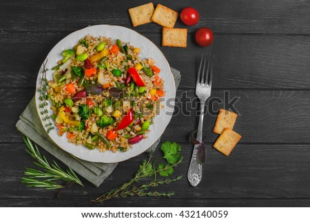 Vegan organic food salad vegetables, cereals, beans, peas, bread, crackers, cherry tomatoes, seasoning for cereal salad greens cilantro, basil, thyme, rosemary, dark black wood background, top view - stock photo