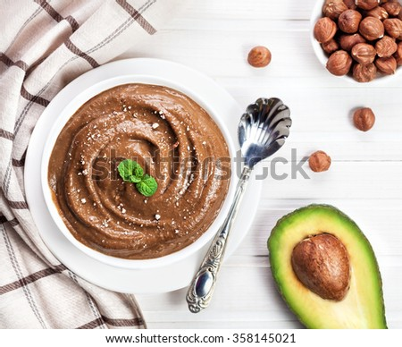 Vegan raw chocolate pudding from avocado, cocoa and hazel milk decorated with mint leaves and crushed nut on white wooden background