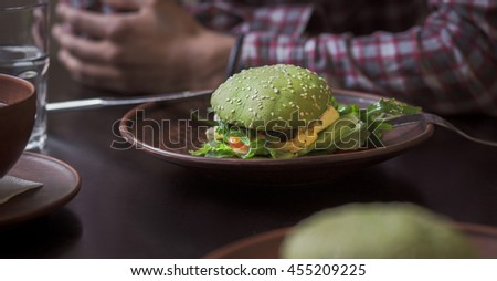 Vegan restaurant or cafe. Picture of vegan dish represented on plate. Vegan hamburger and cherry tomatoes are nice idea for vegan person. - stock photo