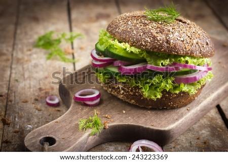 Vegan rye burger with fresh vegetables on rustic background - stock photo