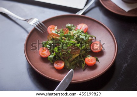 Vegan salad with cherry tomatoes on plate. Closeup picture of vegan dish represented on black wooden table in restaurant or cafe. - stock photo