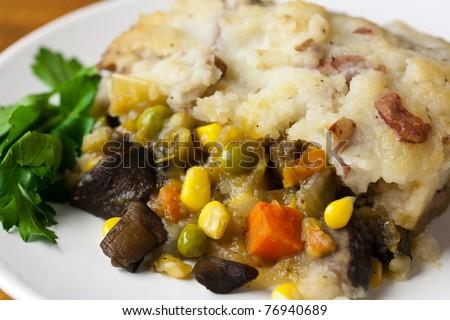 Vegan shepherds pie with a sprig of fresh organic greens - stock photo