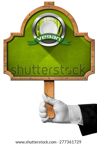 Vegan Sign  / Hand of waiter with white glove holding a wooden pole with an oval sign with wooden frame, vegan symbol with empty white plate and silver cutlery. Isolated on white background - stock photo