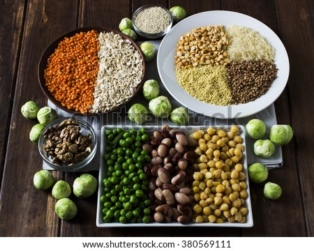 Vegan sources of protein: grains, lentil, beans, nuts and Brussels sprouts on a dark wooden table - stock photo