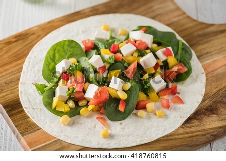 vegan tofu wraps with pepper, corn, tomatoes and spinach  - stock photo