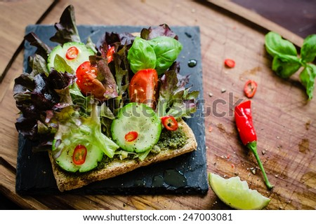 Vegan / vegetarian sandwich with green pesto and fresh vegetables. Selective focus, top view. - stock photo