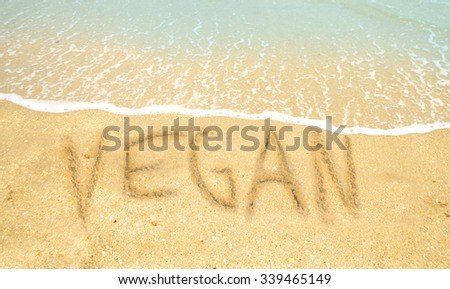 Vegan written in the sand on a tropical beach for a vegan vacation concept - stock photo