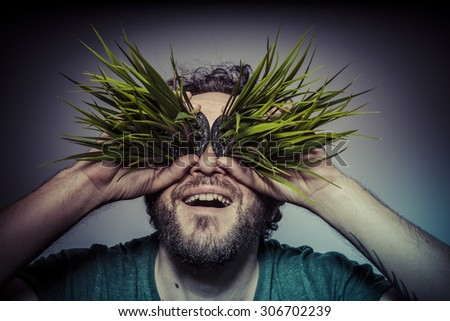 veganism concept man with green grass in the mouth - stock photo