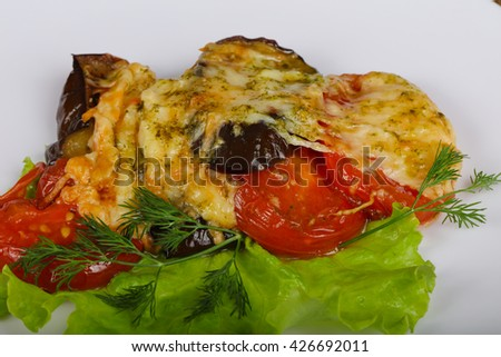 Vegerables baked with cheese served salad leaves and pesto