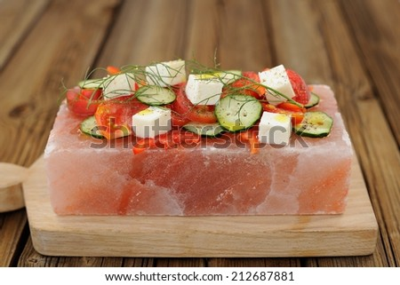 Vegetable and cheese salad served on a block on himalayan pink salt