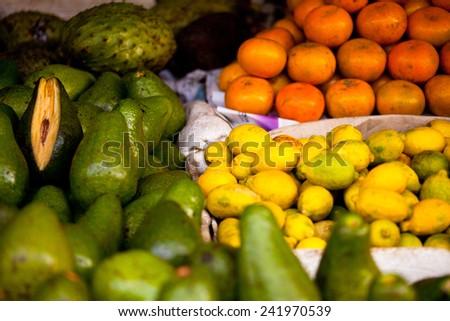 Vegetable and fruit market in Indonesia. Fresh avocados, oranges, lemons.Traditional market, organic food. - stock photo