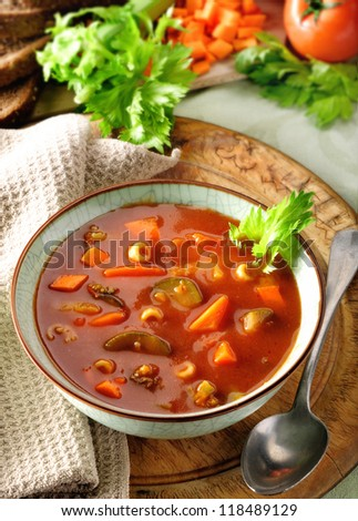 Vegetable and tomato soup. Rustic setting with ingredients in the background. - stock photo