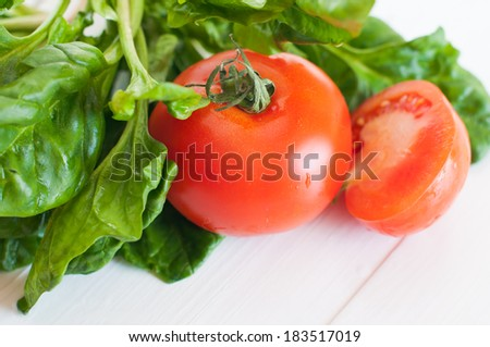 Vegetable background, tomatoes and spinach leaves on a white wooden board, food in kitchen. - stock photo