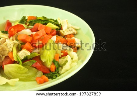 Vegetable boiled consisting of cabbage, carrots, tofu and capsicum on black background.