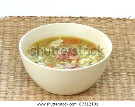 Vegetable cabbage soup in white bowl with bacon pieces - stock photo