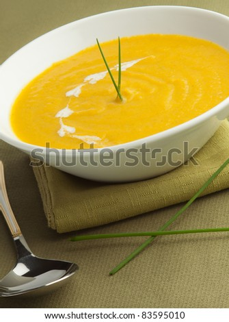 Vegetable cream soup in a white bowl with green background. - stock photo