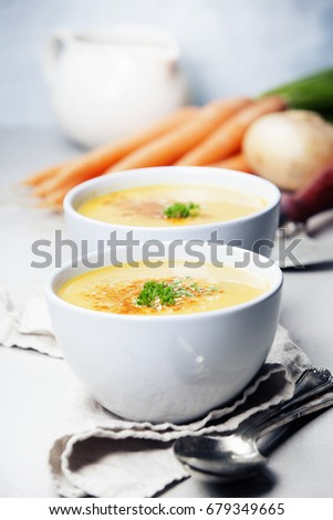 Vegetable cream soup in bowl over grey concrete background, copy space, vertical composition