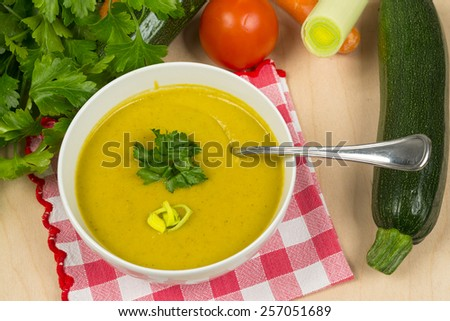 Vegetable cream soup on table with fresh vegetables - stock photo