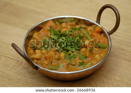 Vegetable curry in a copper dish - stock photo