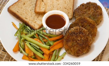 Vegetable cutlet, a delectable combination of mashed potatoes and vegetables, is a crisp and soft Indian potato snack served with glazed vegetables. - stock photo
