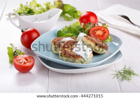 Vegetable cutlets from zucchini, herbs and feta cheese with yogurt sauce. Greek cuisine.
