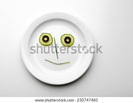Vegetable face on plate isolated on white