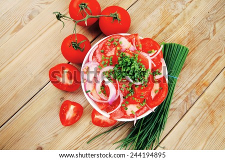 vegetable food : fresh tomato salad in white bowl with bundle of chives and raw tomatoes on twig over wooden table - stock photo