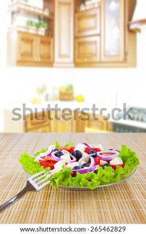 vegetable fresh greek salad with tomatoes union black olives and cheese in glass transparent  glass dish on a wooden bamboo texture table on kitchen set room interior background of units  - stock photo